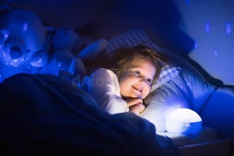 Little Girl Reading A Book In Bed Stock Image - Image of
